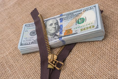 Banknote bundle of US dollar and brown zipper Stock Image