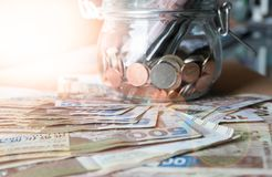 Banknote and coins in glass jar. Hong Kong dollar banknote on the floor and coins in glass jar with lens flare effect Stock Images