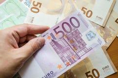 Banknote des Euros 500 in der Hand vor dem hintergrund des Euros, Nahaufnahme lizenzfreie stockbilder