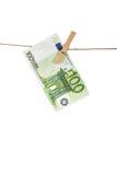 Banknote des Euros 100, die an der Wäscheleine auf weißem Hintergrund hängt Stockfotografie