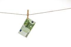 Banknote des Euros 100, die an der Wäscheleine auf weißem Hintergrund hängt Lizenzfreie Stockfotos
