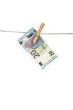 Banknote des Euros 20, die an der Wäscheleine auf weißem Hintergrund hängt Stockbilder