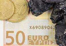 Banknote des Euros fünfzig mit Euromünzen und rohen Kohlennuggets Stockfotos