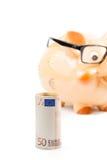 Banknote des Euros fünfzig vor unfocused Sparschwein mit Gläsern, Konzept für Geschäft und sparen Geld Lizenzfreie Stockbilder