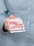 Banknote des Euros zehn im Arm Lizenzfreie Stockfotos