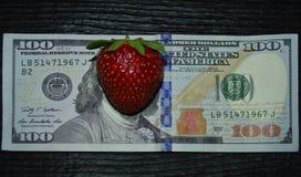 Banknote 100-dollar mit Erdbeeren auf dem Standort von Franklin-` s Gesicht Stockfotos
