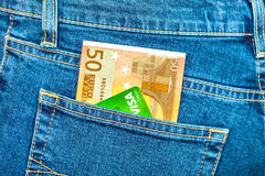 Banknote 50 euro and credit card Visa in back jeans pocket Royalty Free Stock Images