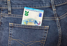Banknote 20 euro sticking out of the back jeans pocket Stock Image