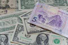 Banknote of five Chinese yuan against background of american dollars. Single banknote of five Chinese yuan against background of american dollars royalty free stock image