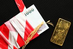 Banknote and gold bar. Banknote bondage by plastic warning tape in the scene appear ear of rice grain and gold bar put on dark background stock photos