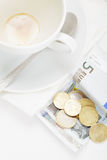 Banknote in payment for coffee above view. Banknote and coins on receipt for coffee payment above view Stock Photo