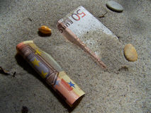 Banknote in sand. Be lucky and find a 50 Euro bill in the sand of a beach royalty free stock photo