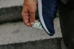 Banknote stuck to sole. Miniature banknote stuck to the sole of a sneaker. Hand feeds remove it from the sole stock photo