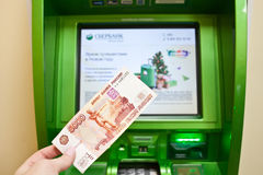 Banknote und Sberbank ATM im Büro Stockfotografie