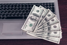 Banknoten über Laptoptastatur-Dollargeld Stockbilder