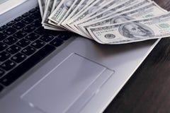 Banknoten über Laptoptastatur-Dollargeld Stockfoto