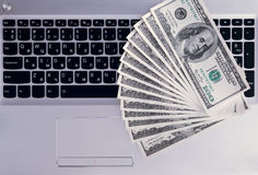 Banknoten über Laptoptastatur-Dollargeld Stockfotografie