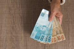 Banknoten der brasilianischen W?hrung: Reais Draufsicht von alte Frau ` s Hand, die Rechnungen behandelt lizenzfreies stockbild