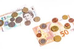 Banknoten des britischen Pfunds und Münzen und Eurobanknoten und Münzen auf Weiß Lizenzfreie Stockfotografie