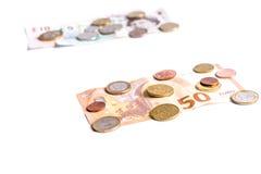 Banknoten des britischen Pfunds und Münzen und Eurobanknoten und Münzen auf Weiß Lizenzfreie Stockfotos