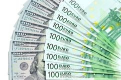 Banknoten von 100 Dollar USA und Euro 100 befinden sich um einen auf anderen als Hintergrund Stockfotos