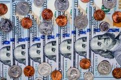 Banknoten von hundert Dollar und von vielen Münzen Stockfotos