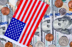 Banknoten von hundert Dollar, von vielen Münzen und von amerikanischer Flagge Lizenzfreies Stockfoto
