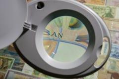 Banknoten von verschiedenen Ländern durch eine Lupe Stockbilder