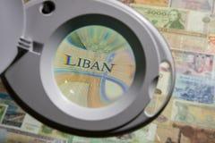 Banknoten von verschiedenen Ländern durch eine Lupe Lizenzfreie Stockbilder