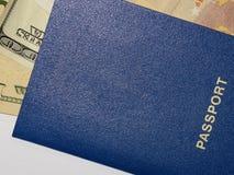 Banknotendollar und -Euros in einem blauen Pass auf einem weißen Hintergrund 2018 Stockbild
