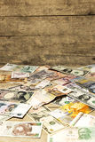 Banknotes by all countries in front of wooden background Royalty Free Stock Photo