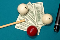 Banknotes on a billiard table. U.S. dollars banknotes on the table, including billiard balls and cue Royalty Free Stock Photo