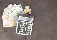 Banknotes and calculator. Euro banknotes on wooden background. Photo for tax, profit and costing. Banknotes with calculator. Euro banknotes on wooden background Royalty Free Stock Photos