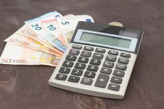 Banknotes and calculator. Euro banknotes on wooden background. Photo for tax, debit and costing. Banknotes with calculator. Euro banknotes on wooden background Stock Images