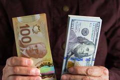Banknotes of canadian currency: Dollar and North American Currency: US Dollars. Old retired person paying in cash. Banknotes of canadian currency: Dollar and stock photo