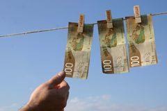 Banknotes on a clothes line. A picture of some 100 dollar banknotes being held to a clothes line with clothes pegs, and a hand reaching out to pluck one of the stock image