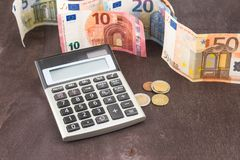 Accounting and business management. Euro banknotes on wooden background. Photo for tax, profit and costing. Banknotes and coins with calculator. Euro banknotes Stock Photo
