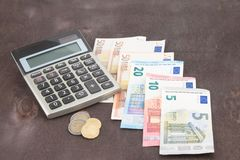 Calculator amd Euro banknotes on wooden background. Photo for tax, profit and costing. Banknotes and coins with calculator. Euro banknotes on wooden background Stock Images