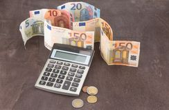 Banknotes and coins with calculator.  Photo for tax, profit and costing. Banknotes and coins with calculator. Euro banknotes on wooden background. Photo for tax Stock Photography