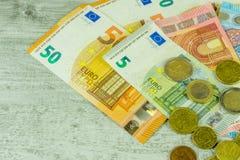 Banknotes and coins in euros Stock Photos