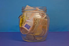 Banknotes and coins in a glass jar stock photography