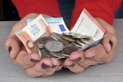 Banknotes and coins in hand stock image
