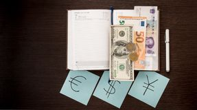 Banknotes, coins, notepad, stickers with currency signs on wooden table. Accounting and taxes. Dollar, Euro, Yuan Renminbi money. Budget calculation Stock Photography