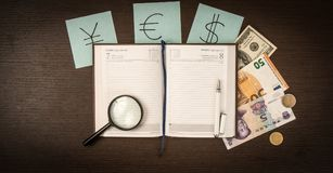International Banknotes, coins, notepad, stickers with currency signs on wooden table. Royalty Free Stock Photography
