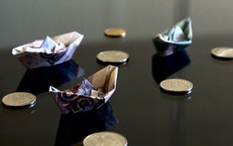 Banknotes and coins. Notes in the form of paper boats among coins Royalty Free Stock Photo