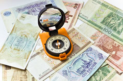 Banknotes and compass. Navigation in the world of Finance. Stock Images