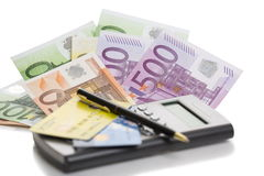 Banknotes, credit cards, calculator and pen. Calculator, credit cards, pen and European  banknotes of 100, 200 and 500 euros over white background. Shallow depth Stock Photos