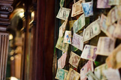Banknotes from different countries glued to the wall. In the interior Royalty Free Stock Photos