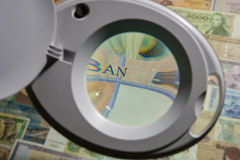 Banknotes of different countries through a magnifying glass Stock Images