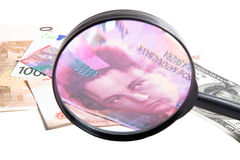 Banknotes of different countries under a magnifying glass isolat Stock Photos